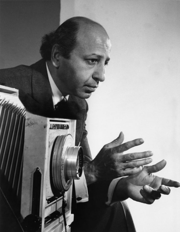 Black and white photograph of the photographer Yousuf Karsh, standing by a large format camera