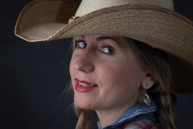 Close up photographic portrait of blonde model, hair in plaits, wearing cowboy hat