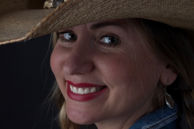 Close up photographic portrait of blonde model, hair in plaits, wearing cowboy hat and smiling.