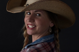 Photograph of blonde model, her hair in plaits, smiling and wearing a cowboy hat.