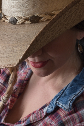 Close up photographic portrait of blonde model, hair in plaits, wearing cowboy hat, face partially obscured by brim of hat.