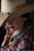 Head and shoulders photographic portrait of blonde model in plaits wearing cowboy hat