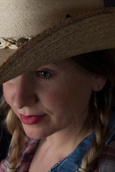 Close up photographic portrait of blonde model in plaits wearing cowboy hat