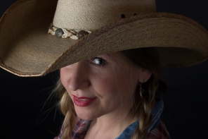 Head and shoulders photographic portrait of blonde model in plaits wearing cowboy hat looking cheeky