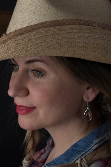 Photographic portrait of blonde model in profile, hair in plaits, wearing cowboy hat