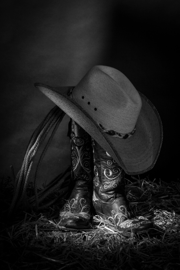 Black and white still life photograph of cowboy boots and hat