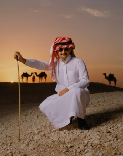 Colour photograph of Saudi Prince in desert, camels in the background, by Michael O'Neill